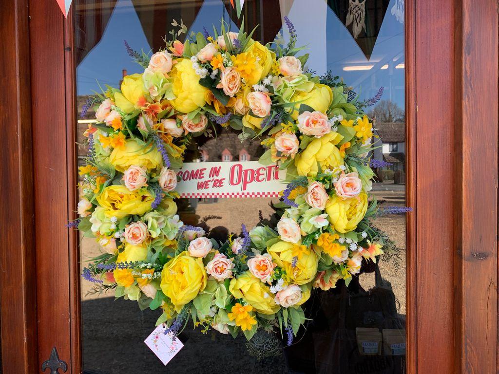 Door wreath saying come in we're open