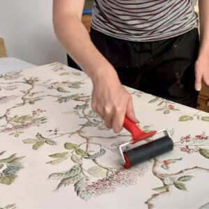 Using a brayer to smooth out the wallpaper after glueing