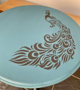 The peacock stencil on top of the table