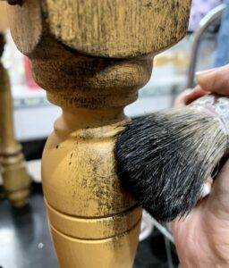 Adding the black wax to furniture with a brush